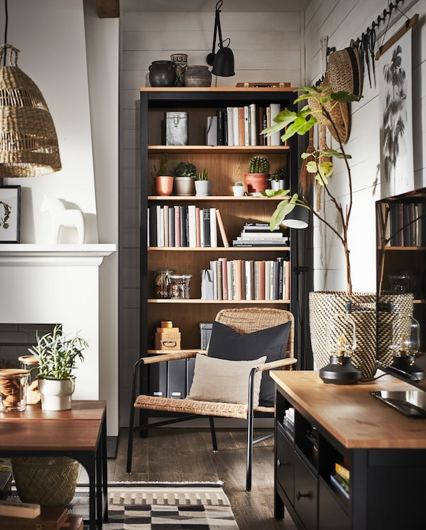 A living room with a TV bench and a bookcase in black-brown/solid pine, an armchair in rattan and items in natural materials.
