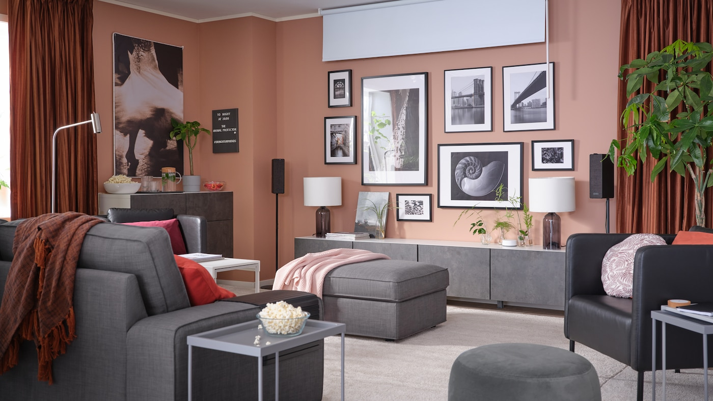 A living room with a wall of framed artworks, a block-out roller blind, room darkening curtains and a 3-seat sofa.