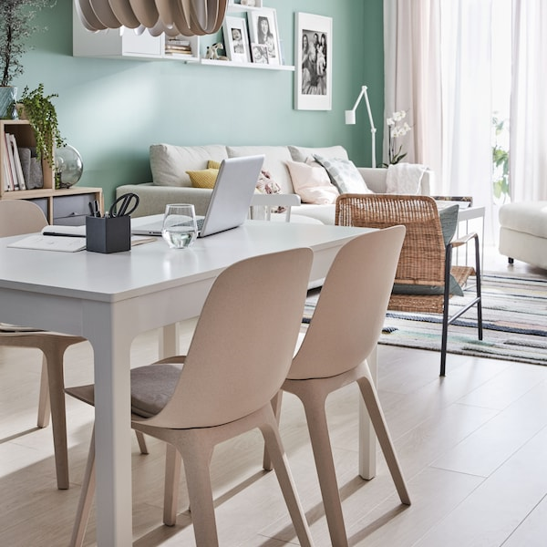 A living room with a white sofa and two armchairs in the background. In focus a white EKEDALEN white table with four chairs.