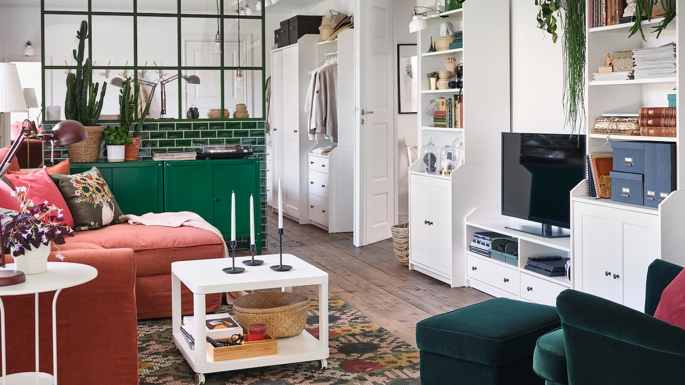 A living room with a wing chair and footstool in dark green, green cabinets and a white HAUGA TV/storage combination.