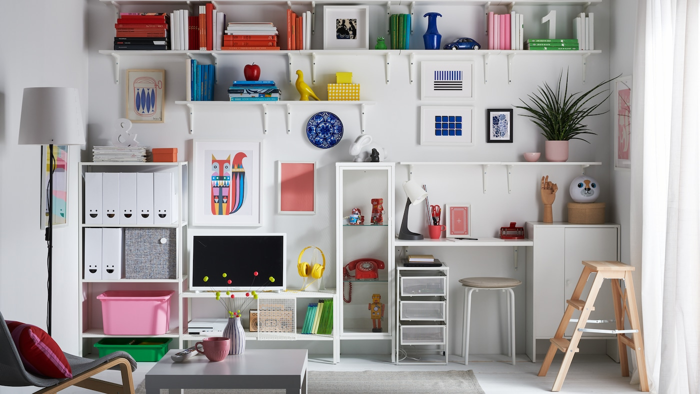 A living room with an entire wall with shelves and cabinets dedicated to books, toys, collectibles and magazine storage.