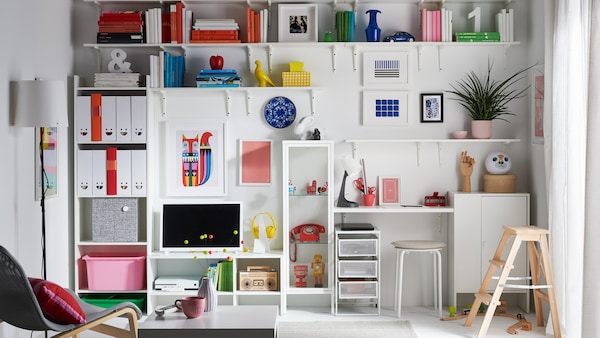 A living room with an entire wall with shelves and cabinets dedicated to book, toys, collectibles and magazine storage.