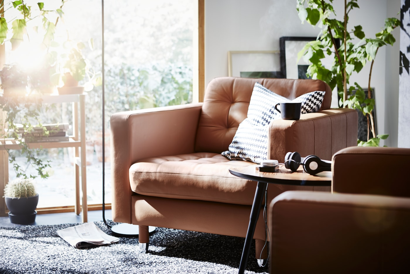 A living room with armchairs and a LANDSKRONAarmchair around a coffee table, with a large window to the right of the sofa.