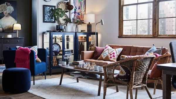 A living room with armchairs and a LANDSKRONAsofa around a coffee table, with a display cabinet to the left of the sofa.