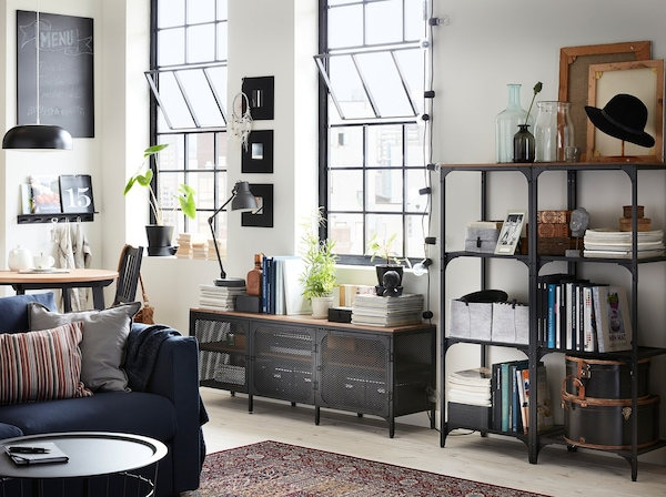 A living room with black FJÄLLBO shelving units and a TV bench in black metal and wood in a converted warehouse building.