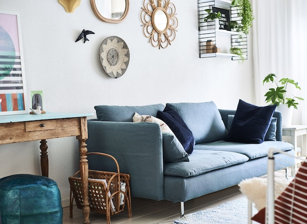 A living room with blue sofa and white walls.