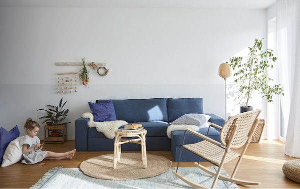 A living room with blue sofa and wicker furniture.
