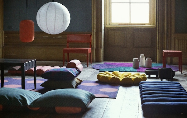 A living room with brightly patterned cushions and rugs scattered on the floor.
