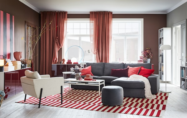 A living room with brown-pink curtains, a red/white rug, a grey sofa and wall-mounted cabinets with red high-gloss doors.