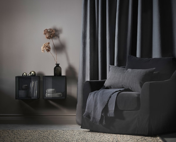 A living room with dark grey armchair and a beige rug.