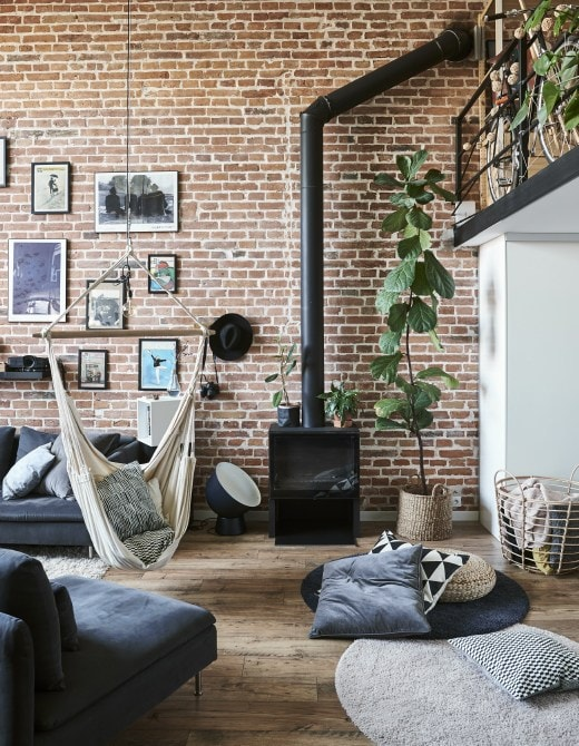 A living room with exposed brick wall and a hammock.