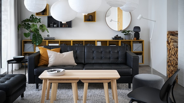A living room with furniture such as MORABO sofa, storage cabinets, tables and lampshades.
