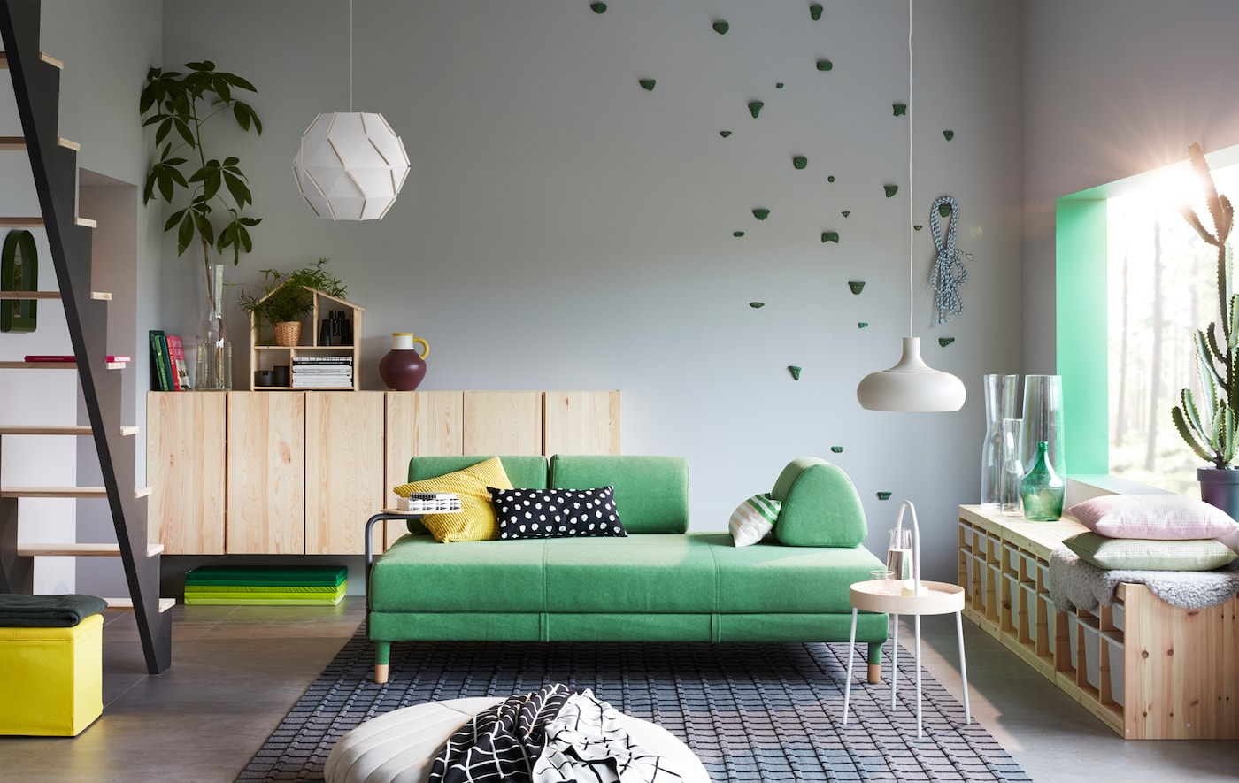 A living room with green sofa, side table and storage cabinets.