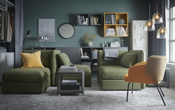 A living room with green VALLENTUNA modular sofa-beds, grey large rugs, grey and yellow cabinets and glass pendant lamps.