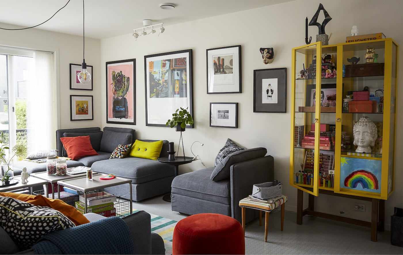 A living room with grey modular sofa, colourful cushions and yellow storage cabinet.