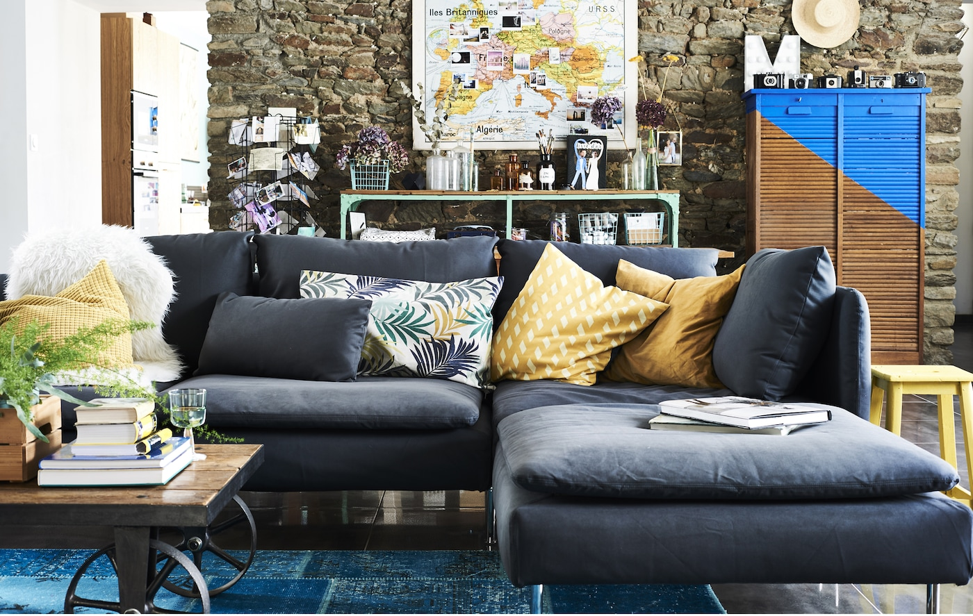 A living room with grey sofa and colourful textiles.