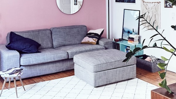 A living room with grey sofa and footstool and white rug with diamond design.
