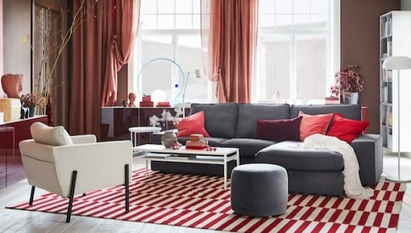 a living room with grey sofa and red rug