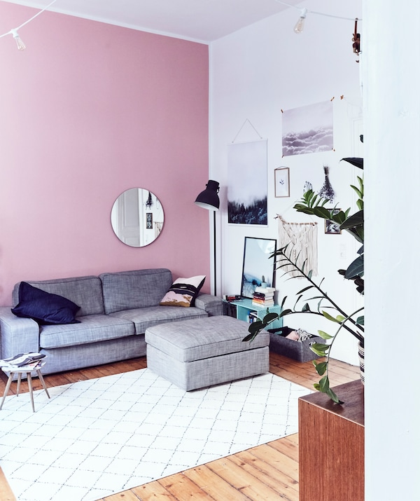 A living room with high ceilings, a pink wall and gray sofa with footstool.