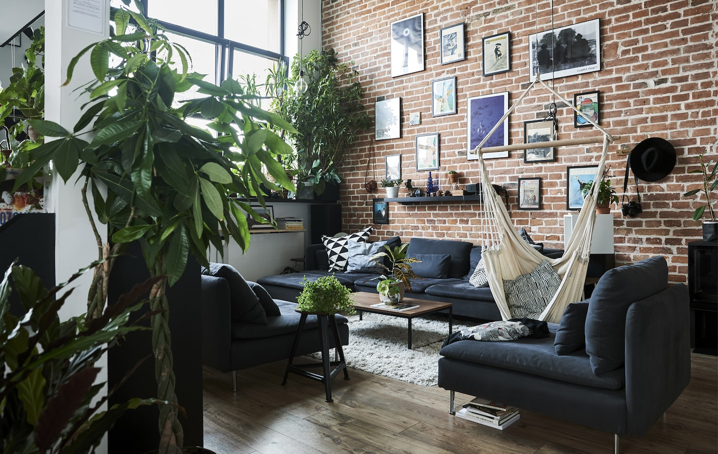 A living room with high ceilings, brick wall and gray modular sofa.