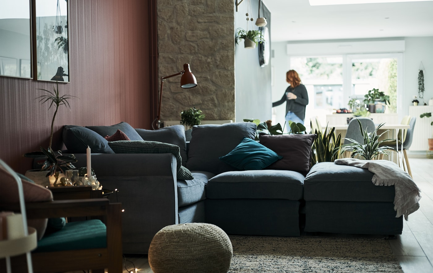 A living room with L-shaped grey sofa and red wall, with a dining area in the background.