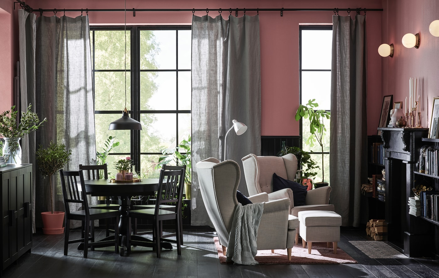 A living room with large windows is decorated in shades of black, mauve and grey-green.