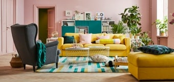 A living room with pink walls and a yellow couch.