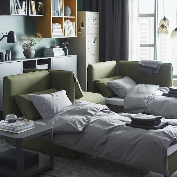 A living room with two green VALLENTUNA sofa-beds that are made as beds.