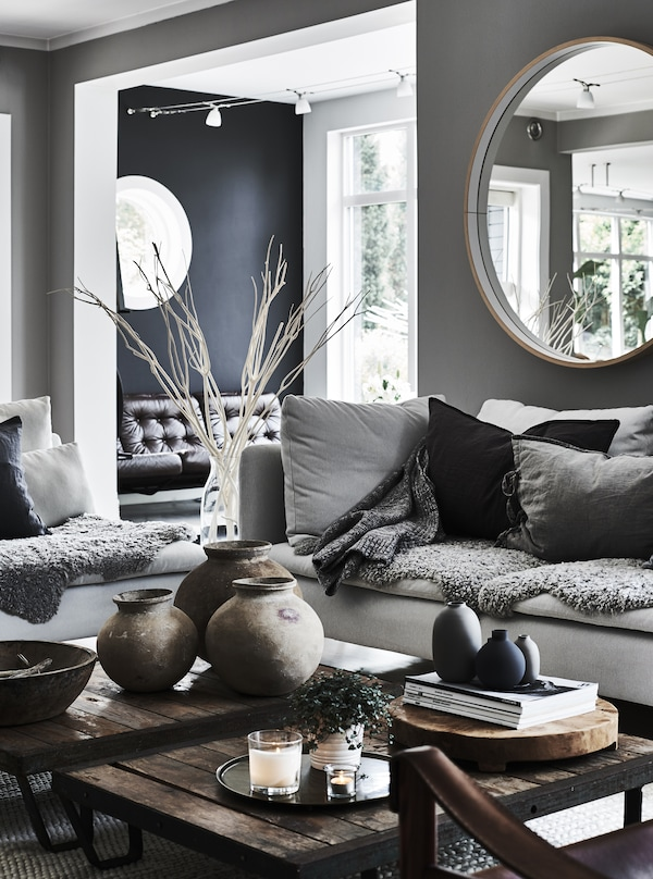A living room with two grey sofas facing inwards decorated with lots of cosy cushions and coffee tables in brown wood.