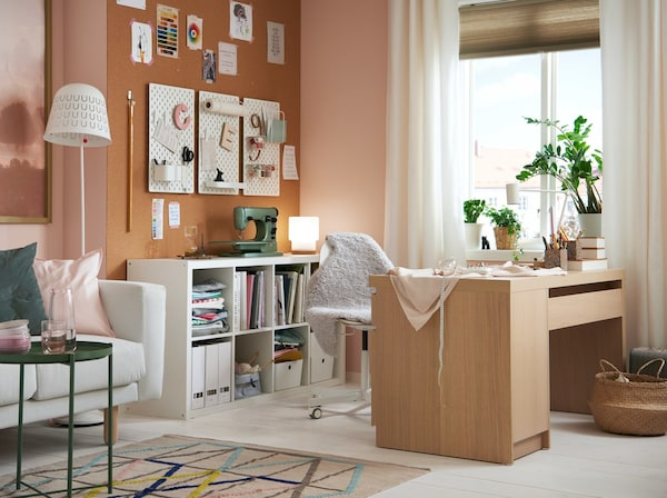 A living room with white furniture and soft pink accents has a creativity corner with a sewing machine and oak desk.