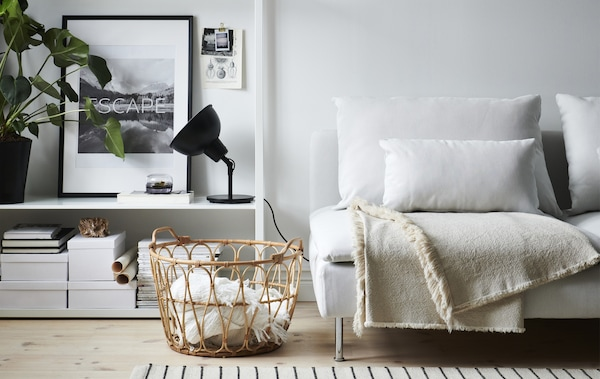 A living room with white sofa, black lamp, open storage unit and wicker basket full of throws.