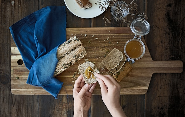 A loaf of seeded bread and jar of honey on a wooden board.