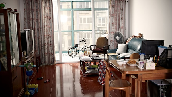 A local living room setting with a black sofa and a coffee table facing the television. The dining table is packed with local dishes and a computer for working at home. Toys are on the floor and a scooter is placed by the cupboard.