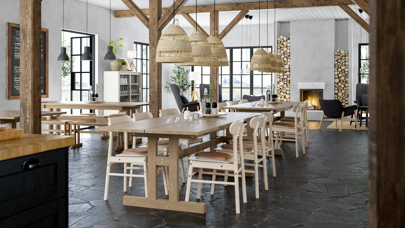 A lodge-style restaurant with long wooden tables, wooden chairs, exposed wooden beams and a fireplace.