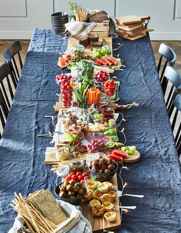 A long blue table, surrounded by blue chairs with a full spread of already-prepared foods for lunch.