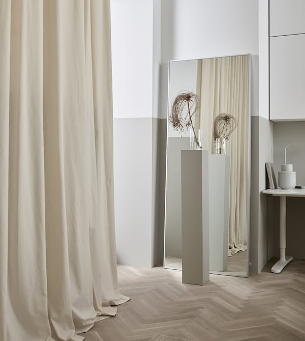 A long cream-coloured curtain hanging along a bare wall softens the look of this living room.