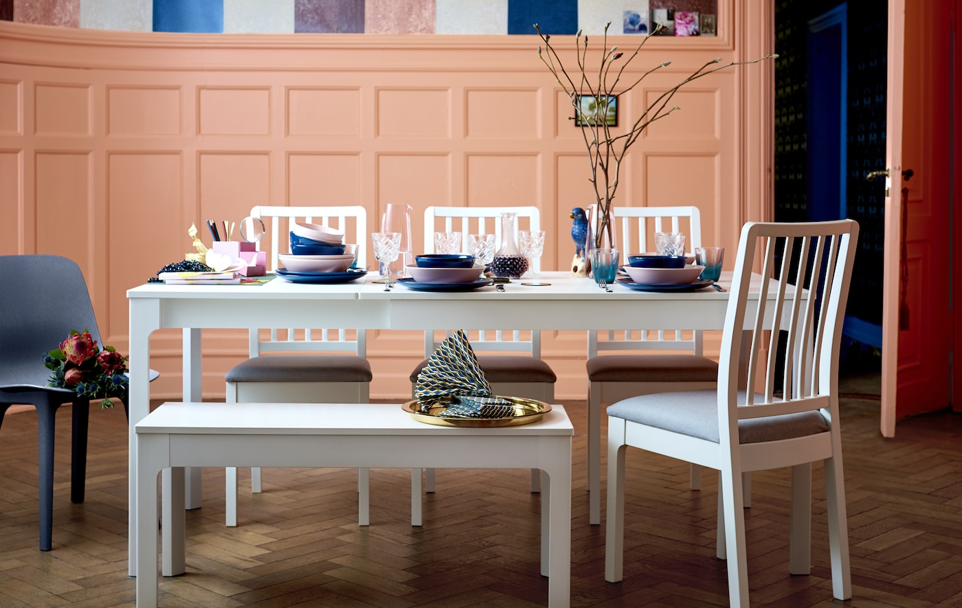 A long white dining table, chairs and bench set with colorful tableware.