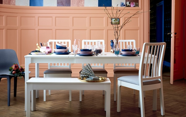 A long white dining table, chairs and bench set with colourful tableware.