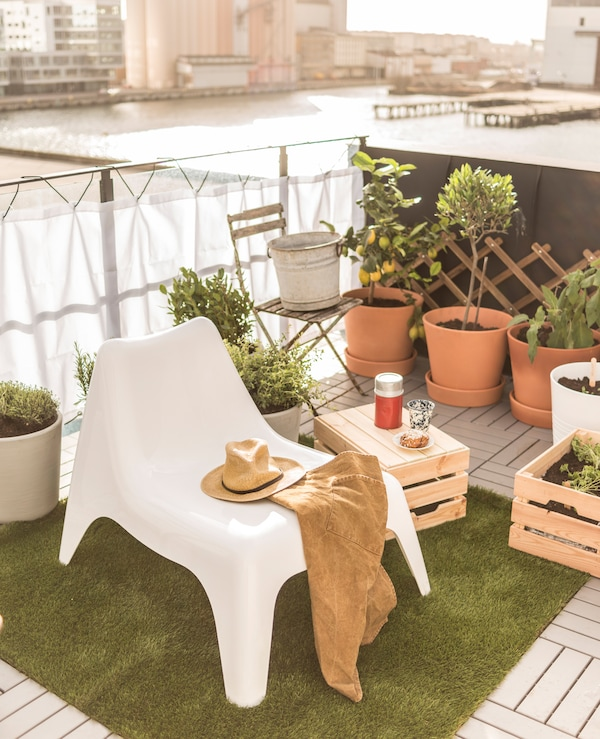 A lounge chair and a wooden box used as a small table create a relaxing space in a rooftop garden.