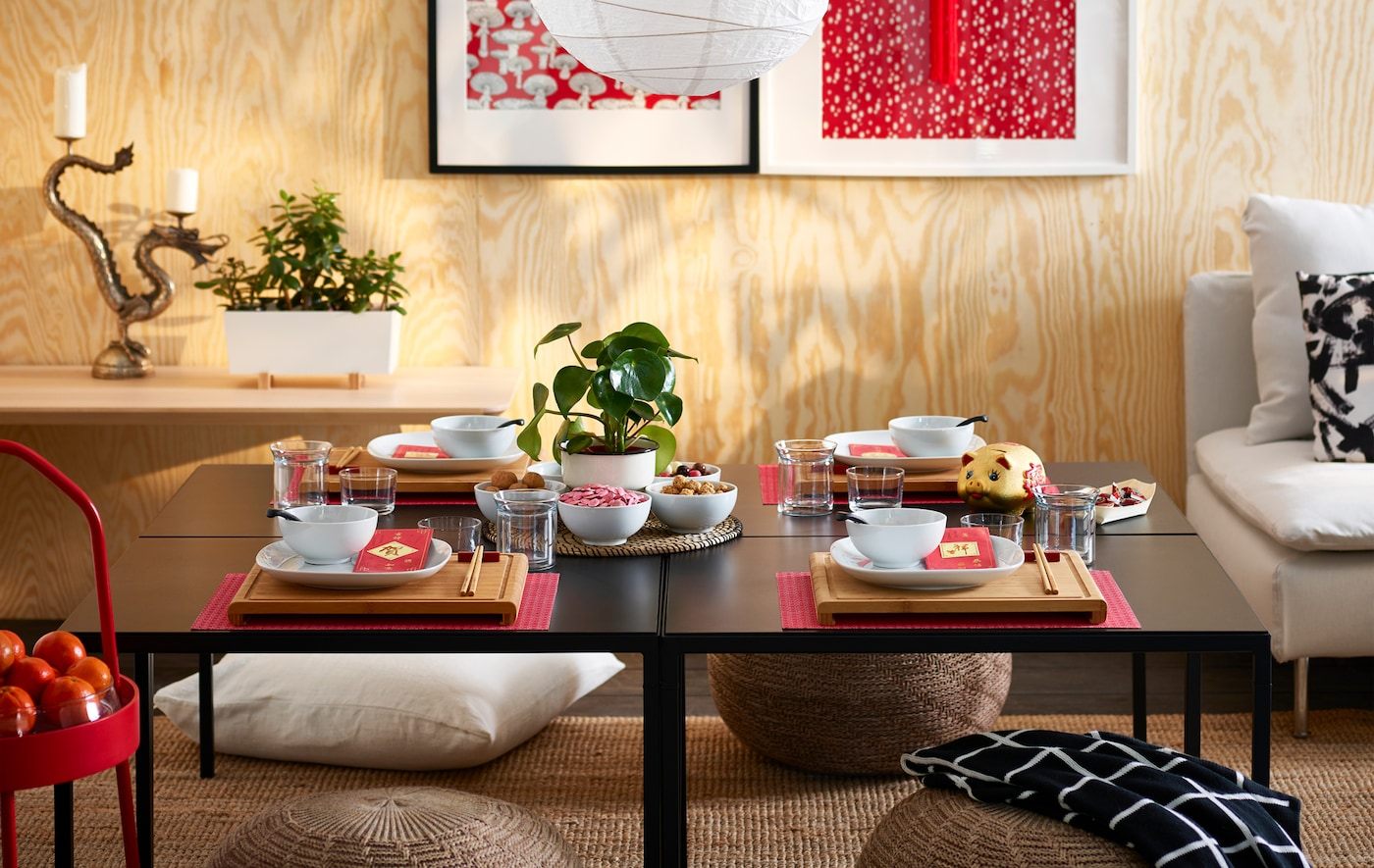 A low black table set with dishware, chopsticks, and drinking glasses in a room with a sofa and a paper lamp hanging above.