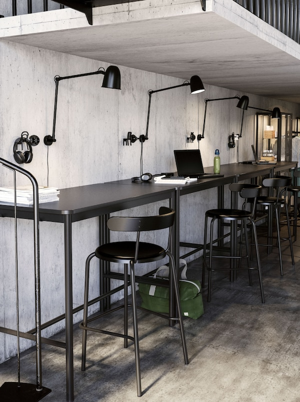 A low-ceilinged co-working space with workstations along a bar, each with a SKURUP work/wall lamp and YNGVAR bar stool.