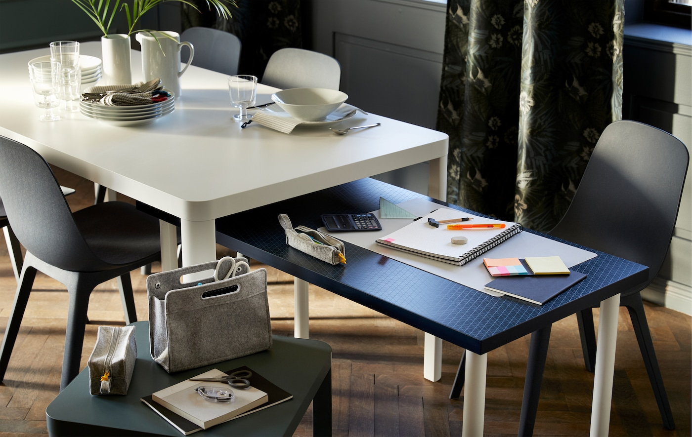 A low table with a blue table top nested underneath a white dining table with chairs surrounding both.