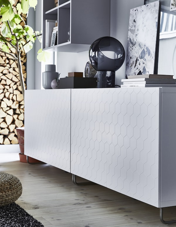 A low white storage unit with honeycomb-patterned door.