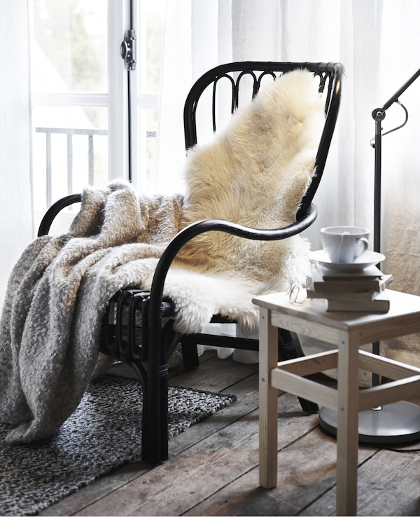 A LUDDE sheepskin and soft grey throw on a black wicker IKEA armchair in a rustic bedroom.