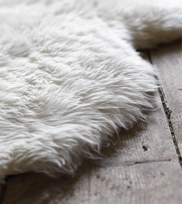 A LUDDE sheepskin on a wooden floor.