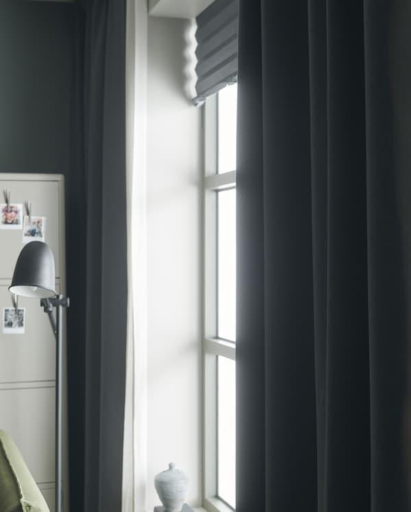 A luz entra através de uma janela com estores de correr em cinzento claro, cortinados transparentes em branco e cortinados semiopacos em cinzento escuro.