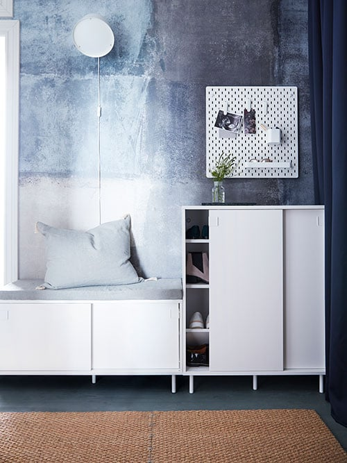A MACKAPÄR bench with storage with a grey pad and cushion on it beside a MACKAPÄR shoe cabinet with a slightly open door.