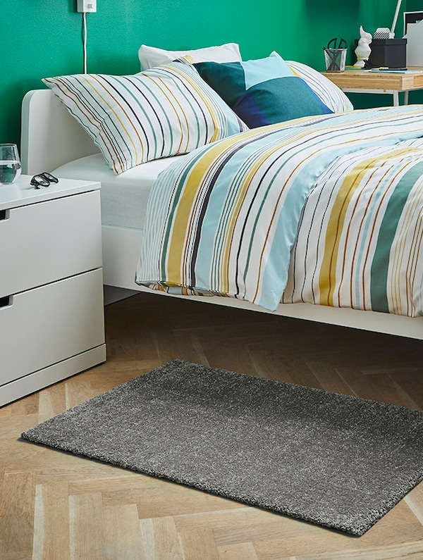 A made bed with a rug and nightstand at bedside.