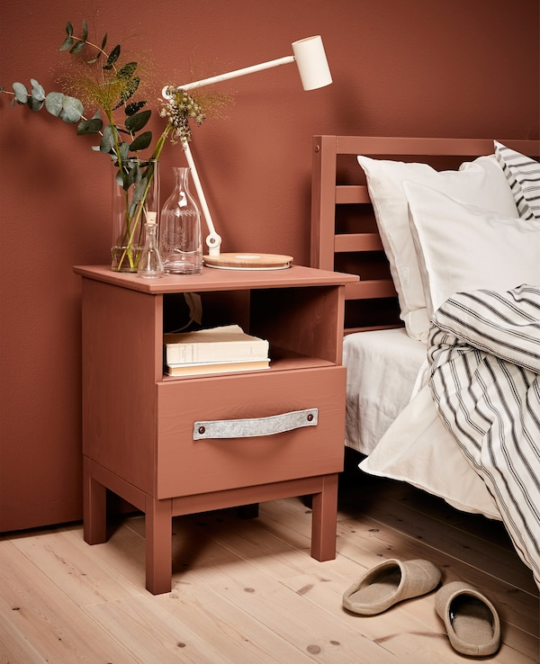 A made-over bedside table with a lamp and some vases on it stands next to a bed.