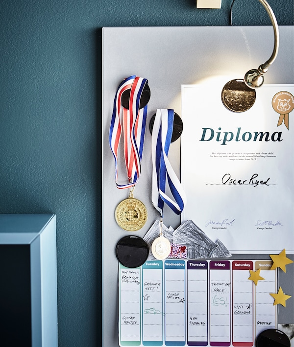 A magnetic board displays medals, a certificate and a weekly schedule.